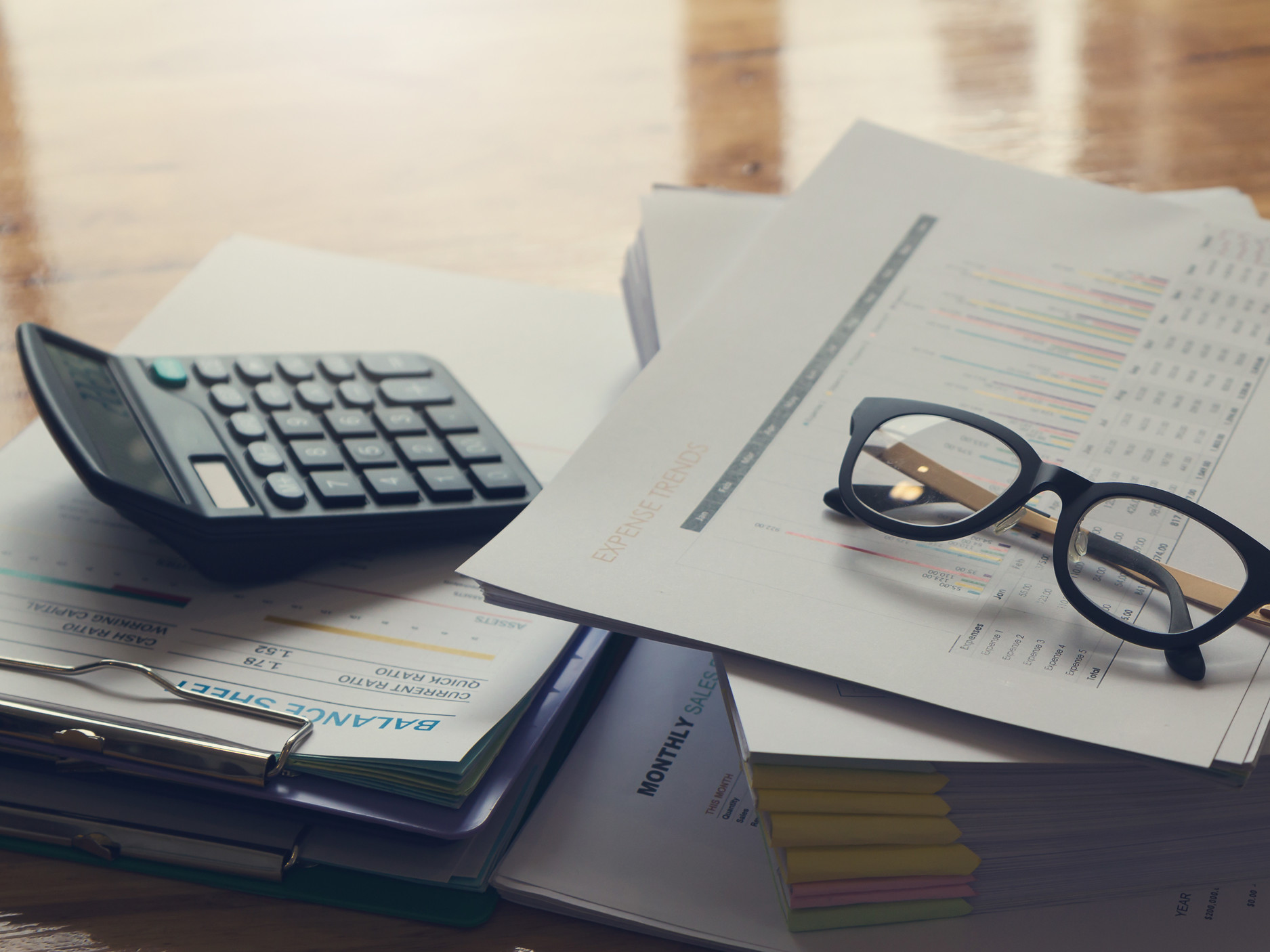Glasses and calculator on desk on top of balance sheet