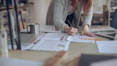 image: worker standing over desk