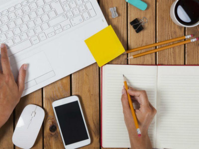 image: worker taking notes at desk